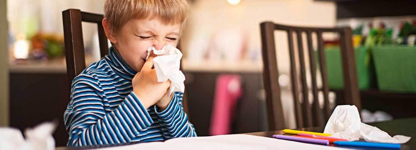 Een kleine jongen snuit zijn neus terwijl hij aan tafel zit met gebruikte tissues om hem heen
