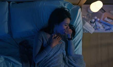 Vrouw in bed hoest 's nachts naast een nachtkastje met medicijnen