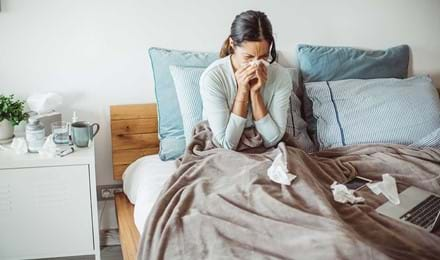 Vrouw snuit haar neus in bed met een tissue