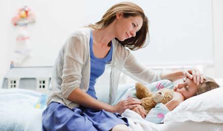 Een moeder verzorgt haar dochter in bed met een kinderverkoudheid