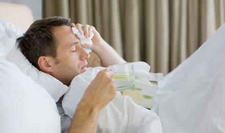 Man ziek in bed met een tissue en kopje thee met citroen