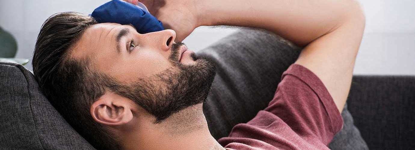 Man in bed legt een kompres op zijn ogen