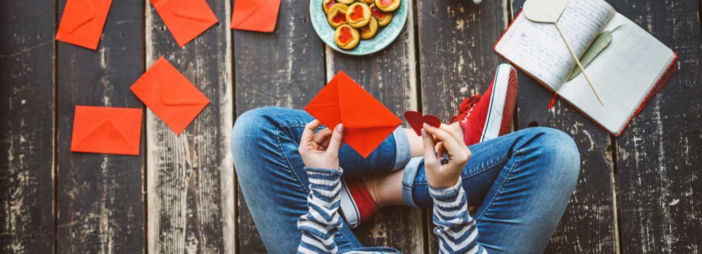 Eine Frau sitzt auf dem Boden und schreibt Karten als selbstgemachtes Geschenk für Valentinstag