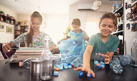 Drei Kinder lernen verschiedenes Plastik und Möglichkeiten zum Recycling kennen, indem sie es sich in der Küche ansehen