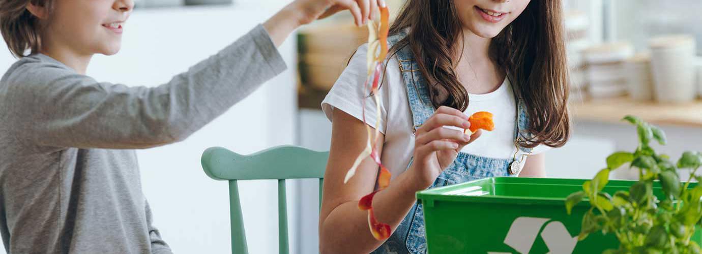Ein junges Mädchen und ein Junge disskutieren, welche Verpackungen biologisch abbaubar sind