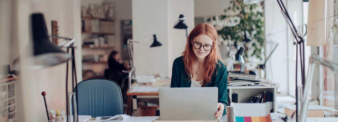 Una donna lavora con il suo computer portatile seduta alla sua scrivania
