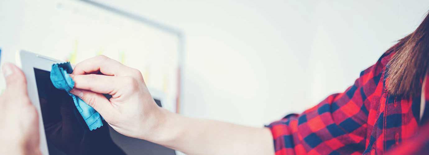 Una donna pulisce lo schermo di un dispositivo mobile o di un computer
