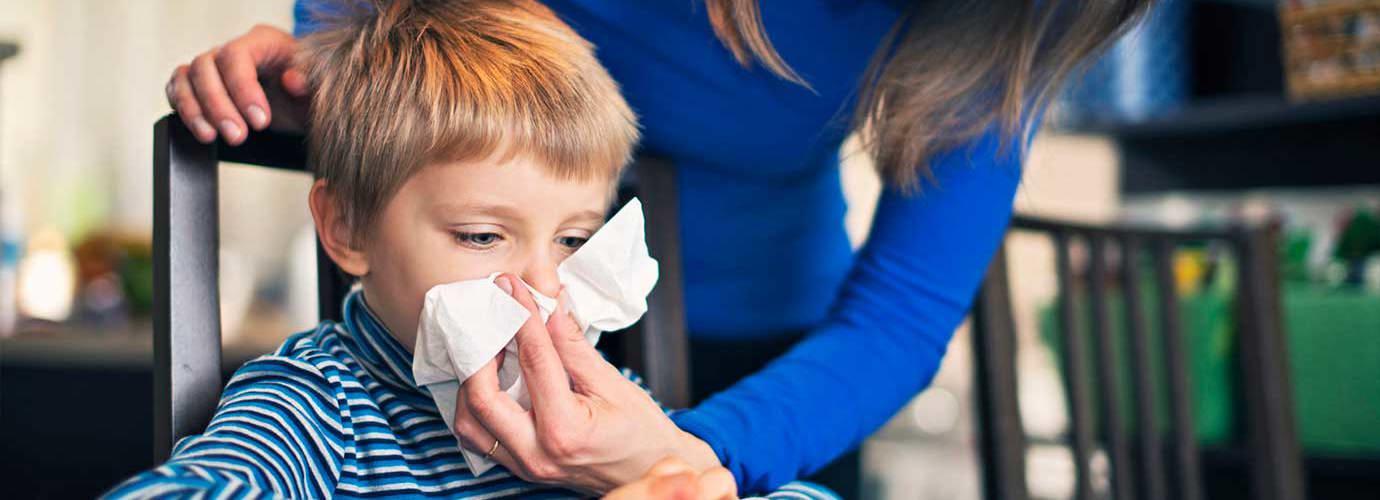 Una madre aiuta suo figlio a soffiarsi il naso