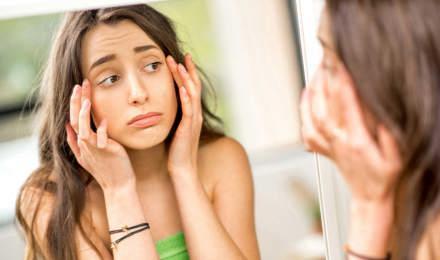 Adolescente controlla allo specchio gli occhi gonfi provocati dalle allergie