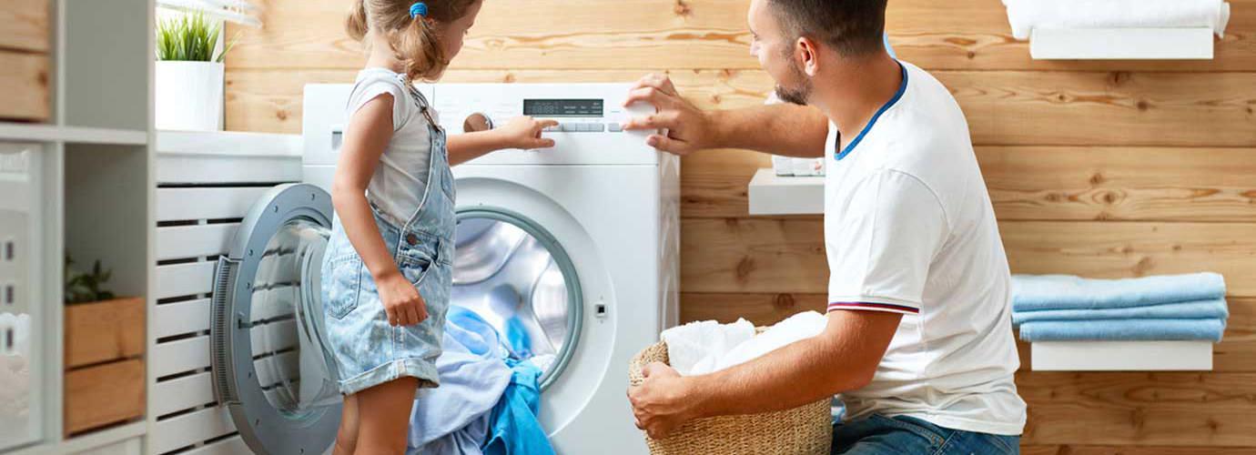 Vater und Tochter waschen gemeinsam die Wäsche