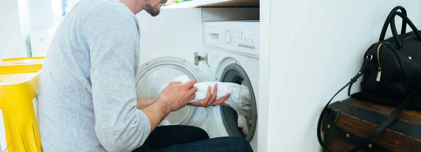 Ein Mann legt Kleidung in eine Waschmaschine