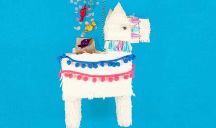 Weiße Lama Pinata bedeckt mit Fransen aus Papiertaschentüchern aus dem Süßigkeiten quellen